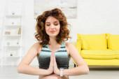 Těhotná žena se usmívá při meditaci v obývacím pokoji