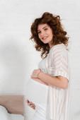 Boční pohled těhotné ženy usmívá na kameru v ložnici