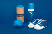baby bottle, toy, baby shoes, jar with baby food ob blue background