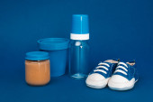 bucket, baby bottle, baby shoes, jar with baby food ob blue background