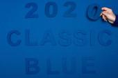 Ausgeschnittene Ansicht einer Frau mit Nummer neben klassischem blauen Schriftzug auf blauem Hintergrund