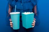 oříznutý pohled na ženu držící popcorn a sodu na modrém pozadí
