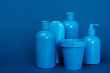 bottles with hair conditioner, shampoo, shower gel, liquid soap and bucket on blue background