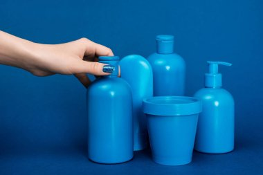 cropped view of woman holding bottle with shampoo on blue background