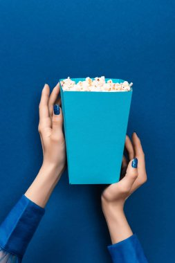 Cropped view of woman holding box with popcorn on blue background stock vector