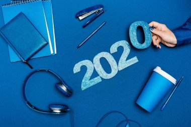 cropped view of woman holding number near notebooks, headphones, pens, stapler on blue background