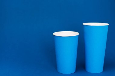 Paper cups with soda on blue background with copy space stock vector