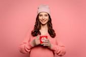 usmívající se dívka v klobouku a rukavicích drží hrnek s teplým nápojem izolované na růžové