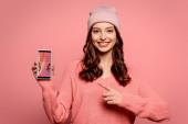 šťastná dívka ukazuje prstem na smartphone s nejlepší nákupní aplikace na obrazovce izolované na růžové