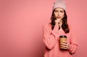 pozorné dívka dívá pryč a dotýká bradu při držení cofee jít na růžové pozadí