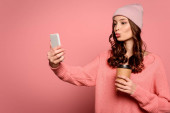attractive girl with duck face expression taking selfie while holding cofee to go on pink background