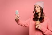atraktivní dívka s kachní tvář výraz přičemž selfie při držení cofee jít na růžové pozadí