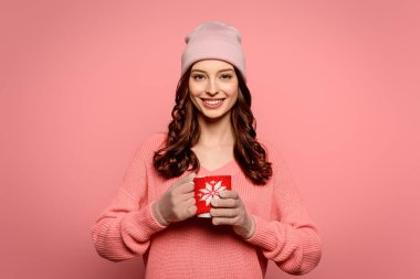Smiling girl in hat and gloves holding mug with warming drink isolated on pink stock vector