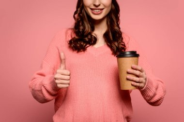 Cropped view of smiling girl holding coffee to go and showing thumb up on pink background stock vector