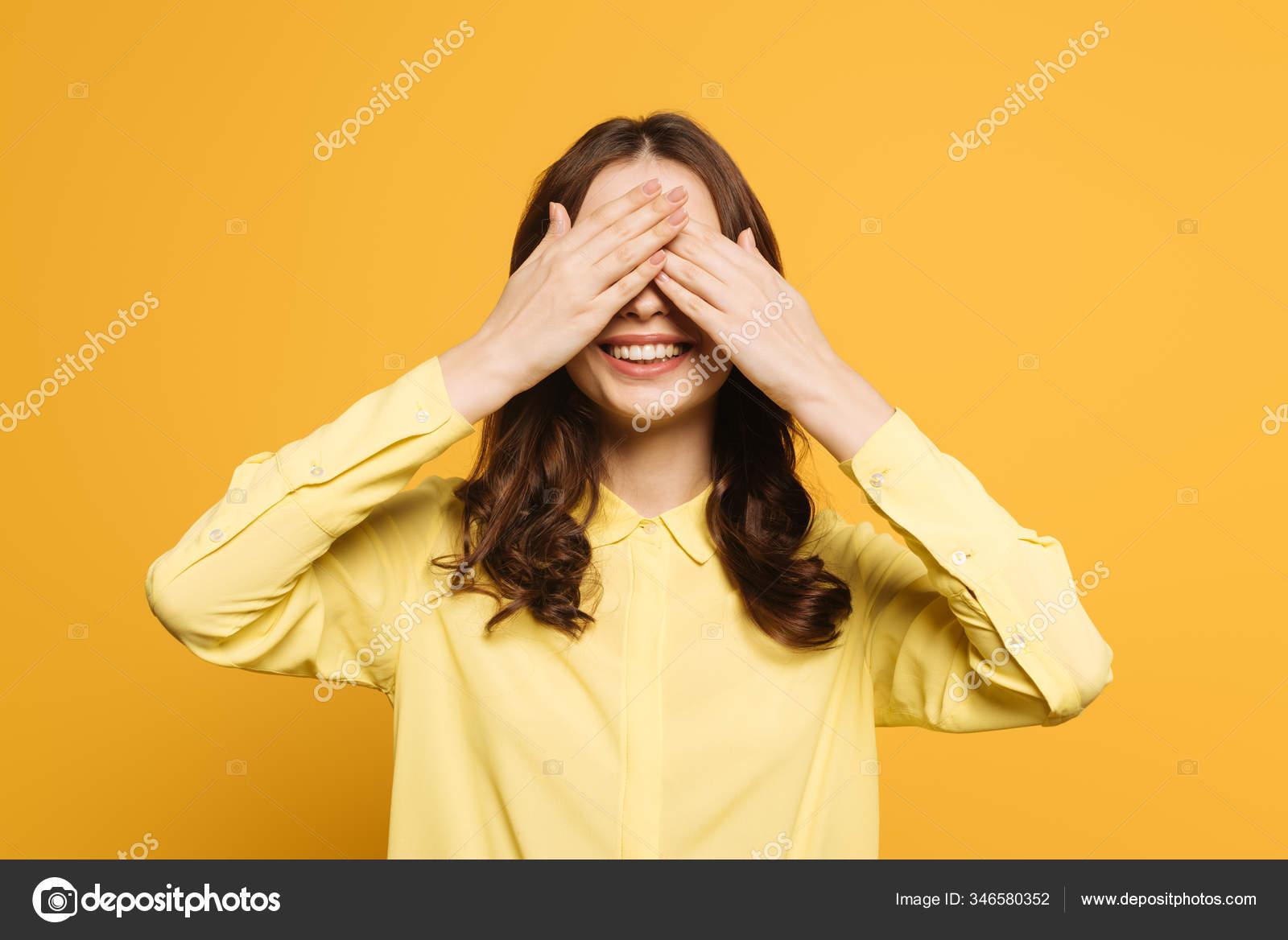 fröhliches mädchen das augen mit der hand auf gelbem