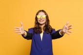 Fotografie fröhliches, stylisches Mädchen in gelber Brille mit Willkommensgeste