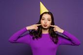fröhliche Mädchen in Partymütze berühren Küken mit Fingern auf lila Hintergrund