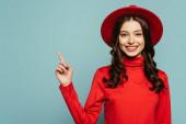 šťastný stylový dívka usmívá na kameru, zatímco ukazuje prstem izolované na modré