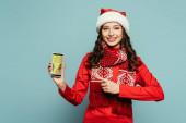 glückliches Mädchen in Weihnachtsmütze und rotem Pullover zeigt mit dem Finger auf Smartphone mit bester Shopping-App auf blauem Hintergrund