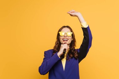 young singer in yellow glasses singing with raised hand isolated on yellow