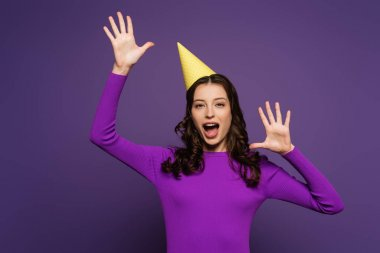 Excited girl in party cap, with open mouth, gesturing with hands on purple background stock vector