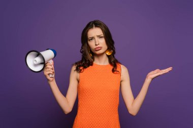 Upset girl showing shrug gesture while holding megaphone and looking at camera isolated on purple stock vector