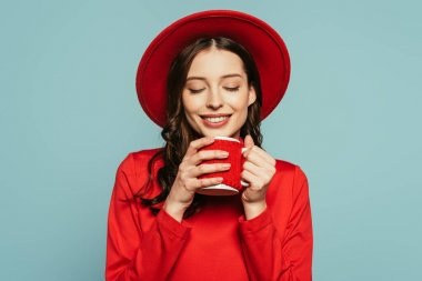 Happy stylish girl enjoying flavor of coffee with closed eyes isolated on blue stock vector