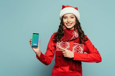1KYIV, UKRAINE - NOVEMBER 29, 2019: smiling girl in santa hat and red sweater pointing with finger at smartphone with Twitter app on screen on blue background stock vector