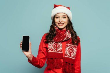 Smiling girl in santa hat and red sweater showing smartphone with blank screen on blue background stock vector