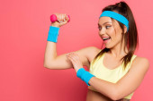 Photo excited sportswoman touching biceps while training with dumbbell on pink background