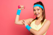 Photo cheerful sportswoman touching biceps while training with dumbbell on pink background