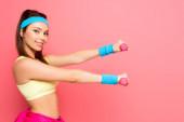 atraktivní mladá sportovkyně školení s činky při úsměvu na kameře na růžovém pozadí