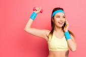mosolygós sportnő beszél okostelefon edzés közben súlyzó rózsaszín háttér