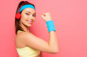 Photo cheerful sportswoman in headphones demonstrating biceps while looking at camera on pink background