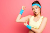 Photo dissatisfied sportswoman touching biceps while looking at camera on pink background