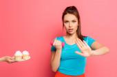 seriózní sportovkyně s činka ukazuje odmítnutí gesto v blízkosti ženské ruky s talířem lahodné cupcakes na růžovém pozadí