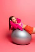 šťastný mladý sportovkyně školení na stříbrném fitness míč při úsměvu na kameru na růžovém pozadí