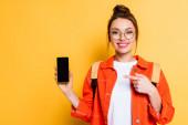usmívající se student ukazuje prstem na smartphone s prázdnou obrazovkou na žlutém pozadí