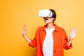 Photo surprised girl gesturing while using vr headset on yellow background