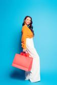 mosolygós divatos lány gazdaság bevásárló táskák és nézi a kamera kék háttér