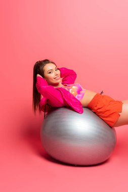 Happy young sportswoman training on silver fitness ball while smiling at camera on pink background stock vector