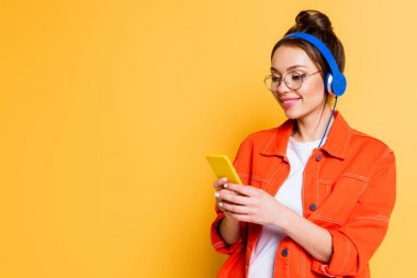 smiling student in headphones chatting on smartphone on yellow background
