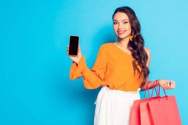 Alışveriş torbaları tutan ve mavi arka planda boş ekranlı akıllı telefonu gösteren mutlu moda bir kız.