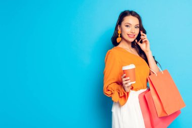 Smiling elegant girl holding coffee to go and shopping bags while talking on smartphone and smiling at camera on blue background stock vector