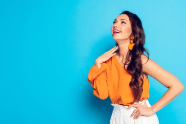 excited fashionable girl looking away while holding hand on hip on blue background