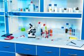 lombikok, kémcsövek és palackok a mikroszkóp közelében a modern laboratóriumban