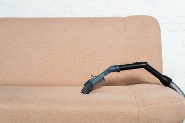 Vacuum cleaner near modern sofa in living room stock vector