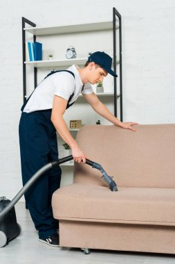 Side view of cleaner in cap removing dust on sofa with vacuum cleaner stock vector