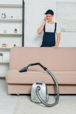 Happy young cleaner in cap and overalls holding vacuum cleaner and talking on smartphone stock vector