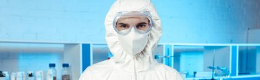 Panoramic shot of scientist in hazmat suit, medical mask and goggles looking at camera stock vector
